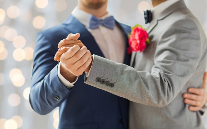 happy male gay couple holding hands and dancing