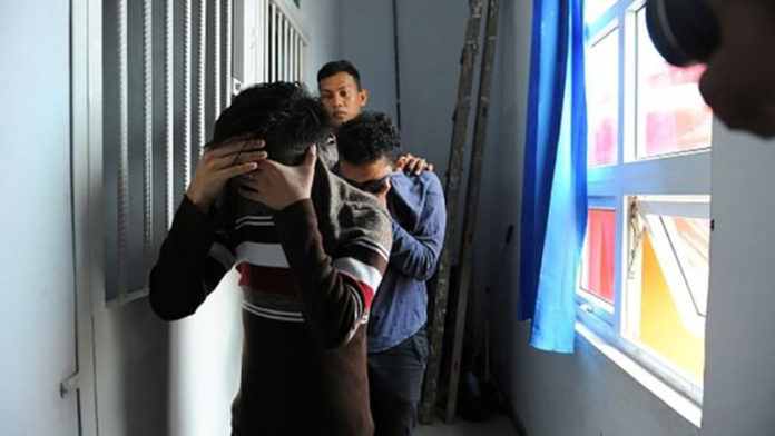 A police officer escorts two men accused of having gay sex into a holding cell prior to their trial at sharia court in Banda Aceh AP