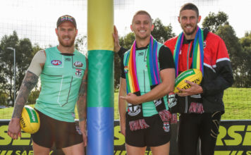 Saints players Tim Membrey, Seb Ross and Tom hickey (L-R) with te custom rainbow goal wraps to be used at the pride match this weekend.(Supplied)