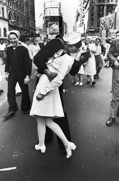 """Original caption: """"In New York's Times Square a white-clad girl clutches her purse and skirt as an uninhibited sailor plants his lips squarely on hers"""". Photo by Alfred Eisenstaedt."""