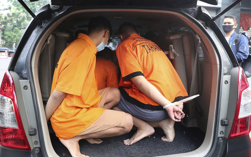 Men arrested in an Indonesian raid of a gay party sit inside a vehicle after a news conference at Jakarta police headquarters in Jakarta