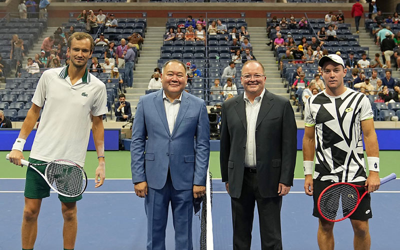 Dr. Bernard Camins from Mt. Sinai Hospital and the USTA Medical Advisory Group and his husband Brian Wigley participate in the coin toss for the men's singles match between Daniil Medvedev and Dominik Koepfer at the US Open on Pride Day
